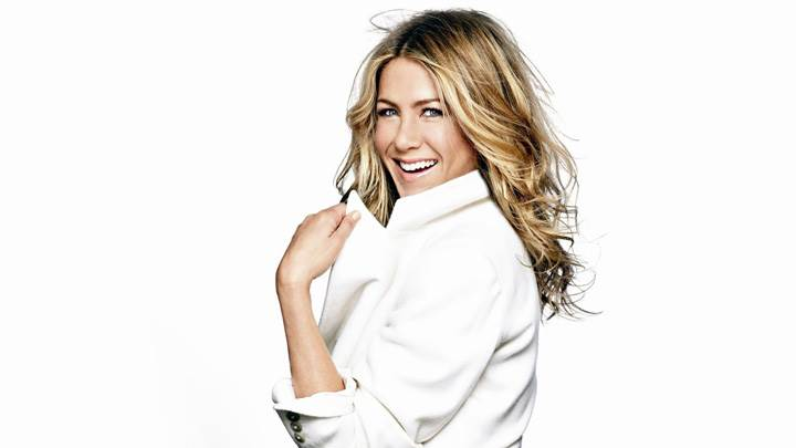 Jennifer Aniston Laughing Side Pose In White Coat N White Background